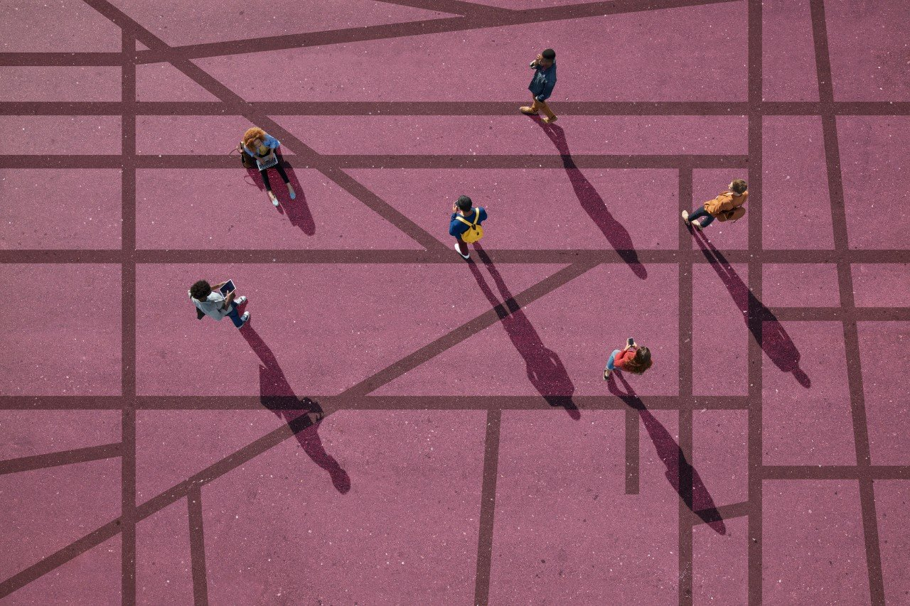 Group of young adults, photographed from above, on various painted tarmac surface, at sunrise.